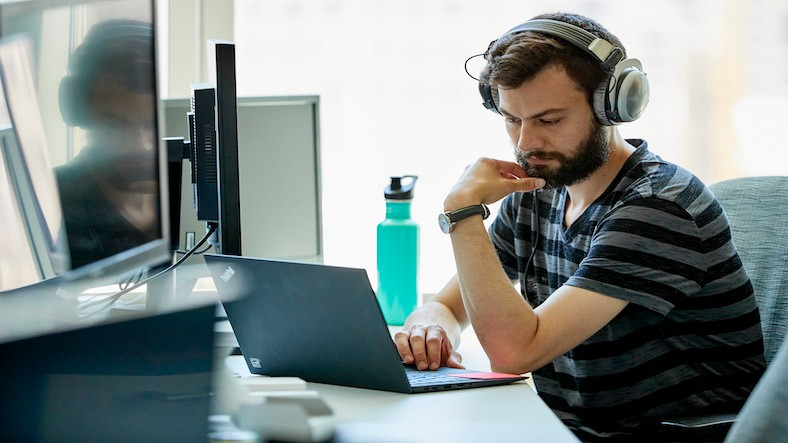 Man listening to head phones while on a computer